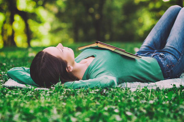 Brunette in a green shirt, lying on her back in the grass with a book lying face down on her stomach