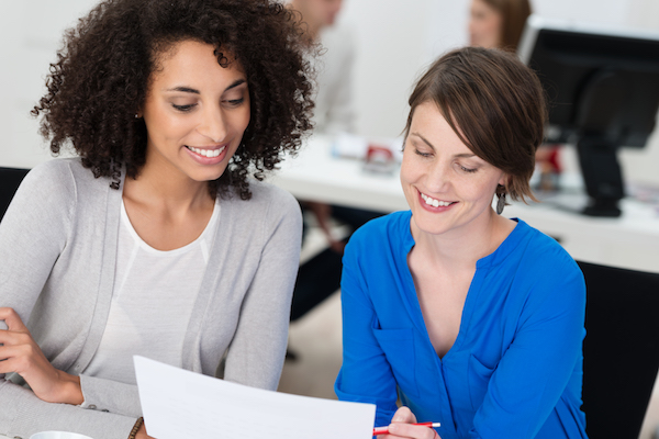 Two smiling businesswomen working on a document as they sit close together at a desk in the office, one is Caucasian and the other is African American