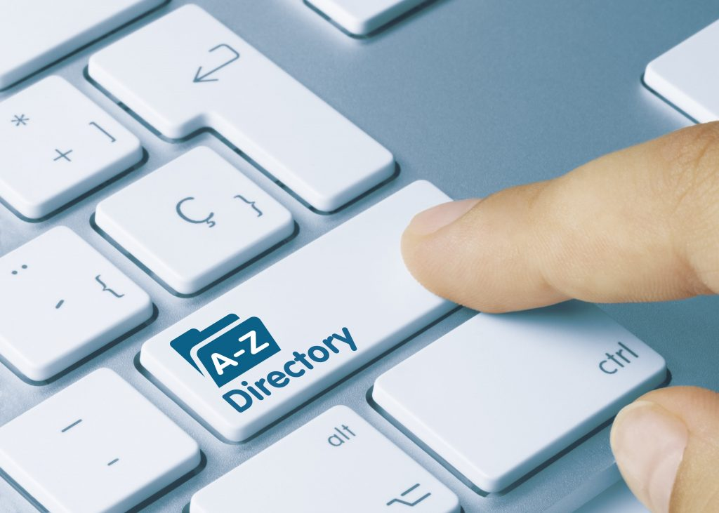 "A pointer finger pressing a key on a keyboard that says ""A-Z Directory"" about to search for therapist directories"