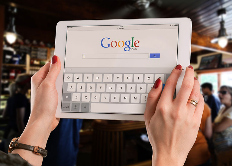 Woman holding a tablet logged onto Google ready to search for therapist directories.