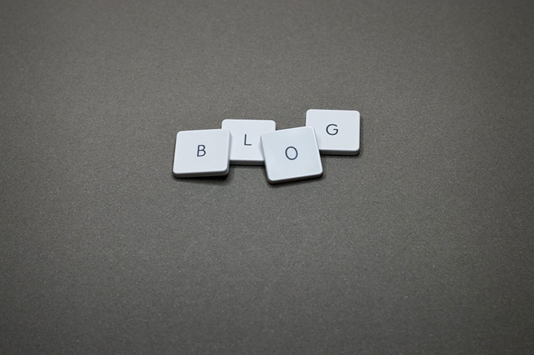 "A picture of the four letters ""B,"" ""L,"" ""O,"" and ""G"" each on a small plastic square laying next to each other to spell the word ""Blog."""