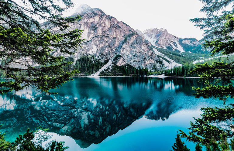 A sky blue lake in a mountain valley reflects a crag amid a field of evergreen trees, creating a calming effect on the viewer.