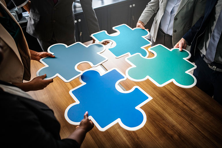 four business people standing around a wooden table, eaching holding a puzzle piece and fitting the pieces together, symbolizing strategy development.
