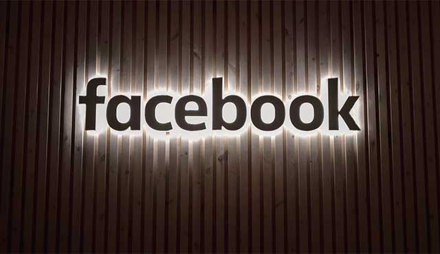 Facebook logo illuminated on a corrugated background.