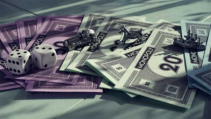 An image of the board game Monopoly's play pieces, including money and game pieces.